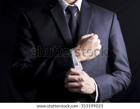 Businessman Fixing Cufflinks his Suit - stock photo