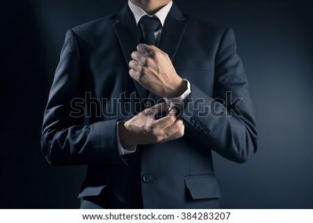 Businessman Fixing Cufflinks his Suit - stock photo