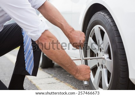 Businessman fixing tire of his car - stock photo