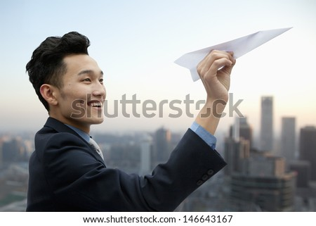 Businessman Flying Paper Airplane - stock photo