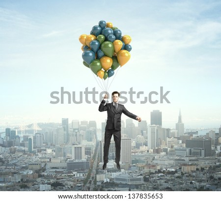 businessman flying with air balloons over the city - stock photo