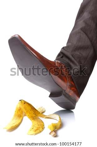 Businessman foot about to slip and fall on a banana skin - stock photo