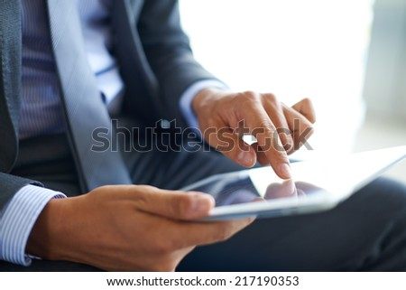 Businessman forefinger pointing at document in touchpad - stock photo