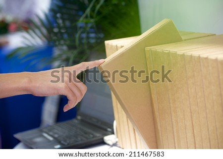 Businessman gets brown folder from row of office folders - stock photo