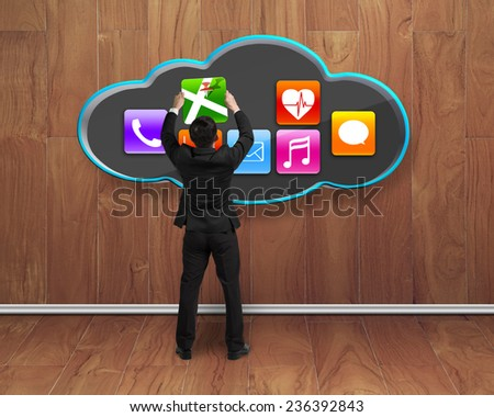 businessman getting map app icon from black cloud with wooden wall and floor interior background - stock photo