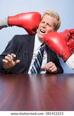 Businessman getting punched - stock photo