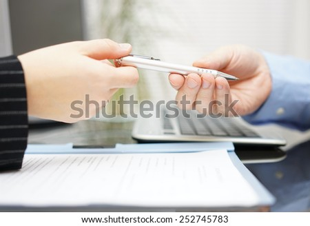 Businessman give client pen to sign the contract in office - stock photo