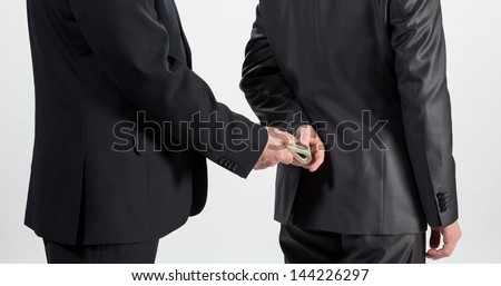 Businessman giving a bribe, neutral background - stock photo