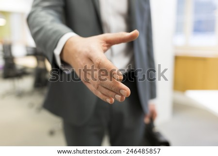 Businessman giving a hand in office - stock photo