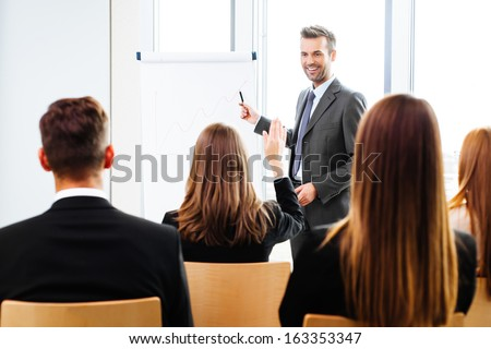Businessman giving a presentation on flipchart. Teamwork concept - stock photo