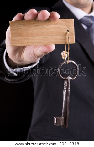Businessman giving a special key to someone (put your text on the wooden keychain) - stock photo