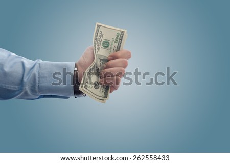 Businessman giving away a fistful of dollars with copy space - stock photo