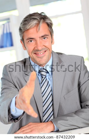 Businessman giving handshake to client - stock photo