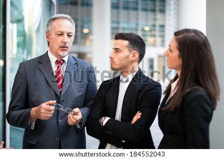 Businessman giving instructions to his colleagues - stock photo
