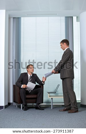 Businessman giving paper to colleague in office - stock photo