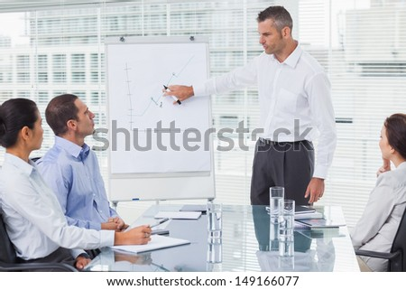 Businessman giving presentation to his colleagues in bright office - stock photo