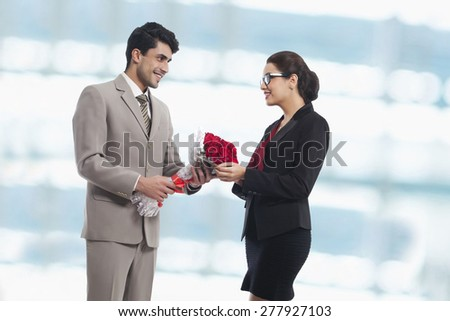 Businessman giving rose bouquet to female colleague in office - stock photo