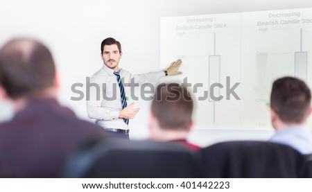 Businessman giving talk on stock trading workshop. Business executive delivering a presentation to his colleagues during meeting or in-house business training. - stock photo