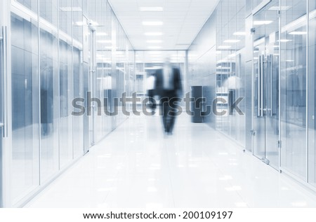 businessman goes along a corridor at modern office - stock photo