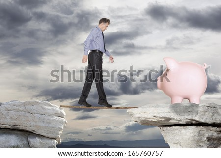 Businessman goes over the precipice to the pig piggy bank - stock photo