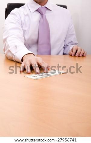 businessman grabbing a dollar bill in his desk (selective focus) - stock photo