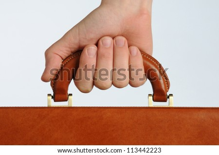 businessman gripping the handle of a brown leather briefcase - stock photo