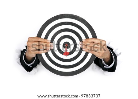 Businessman hand breaking through a paper wall holding a dart board - stock photo