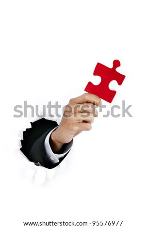 Businessman hand breaking through a paper wall holding a piece of puzzle - stock photo