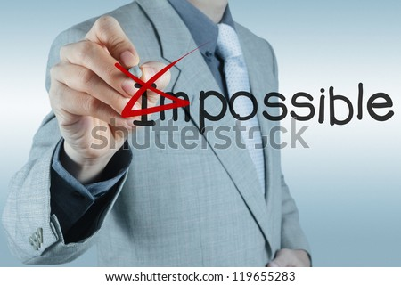 Businessman hand changing the word impossible into possible - stock photo