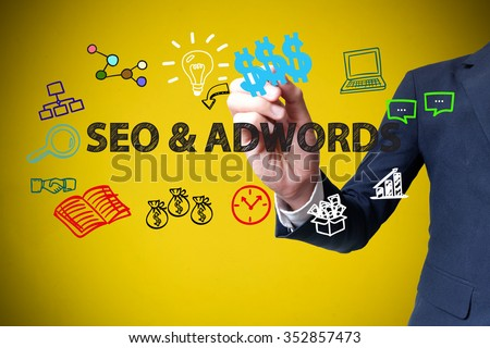 businessman hand drawing and writing SEO & ADWORDS on yellow background , business concept , business idea - stock photo