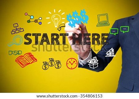 businessman hand drawing and writing START HERE on yellow background , business concept , business idea - stock photo