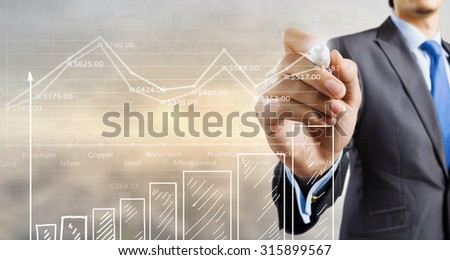 Businessman hand drawing increasing graph on media screen - stock photo
