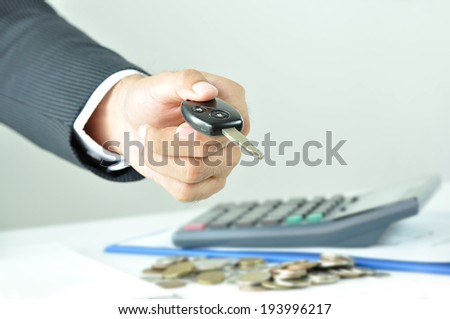 Businessman hand giving a car key - car rent, sale & pawn concept - stock photo