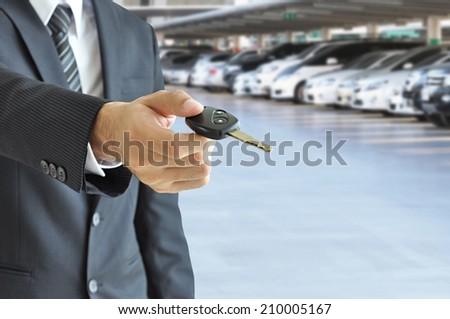 Businessman hand giving a car key - car sale & rental business concept - stock photo