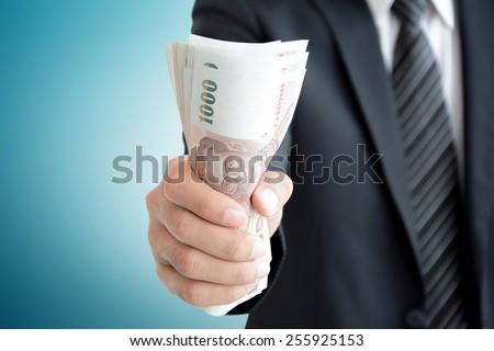 Businessman hand grabbing money - Thai Baht (THB) - stock photo
