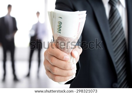 Businessman hand gripping money, Thai Baht (THB) bills - investment, success and profitable business concepts - stock photo