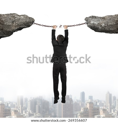 Businessman hand hanging on the broken rusty iron chains connect two cliffs with urban scene skyline background - stock photo