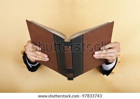 Businessman hand holding a book breaking through a paper wall - stock photo
