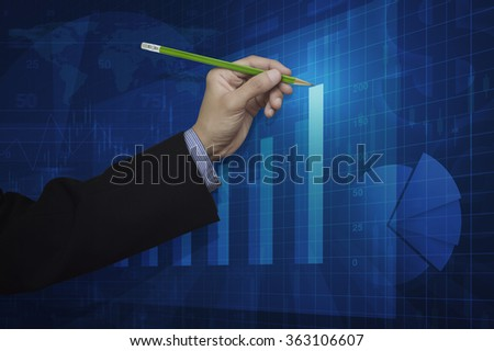 Businessman hand holding a pencil pointing at growth graph, Success business concept, Elements of this image furnished by NASA - stock photo