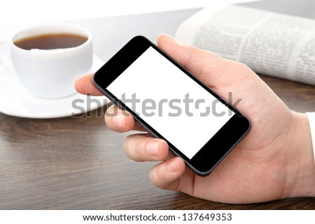 businessman hand holding a phone with isolated screen against the background of the table in the office - stock photo