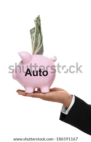 Businessman hand holding a piggy bank for auto expenses and money coming out of the top side view - stock photo