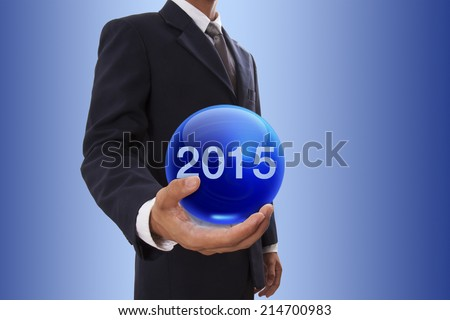 Businessman hand holding blue crystal ball with number 2015. - stock photo