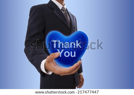 Businessman hand holding blue heart bubble with thank you word - stock photo