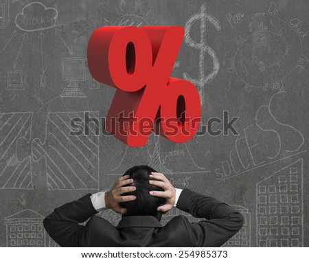 Businessman hand holding head with red percentage signs on doodles wall background - stock photo