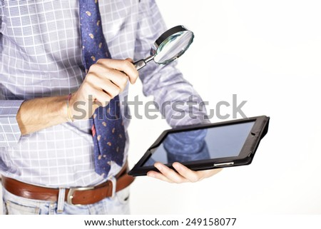 Businessman hand holding magnifier over tablet pc - stock photo