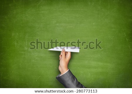 Businessman hand holding paper plane on front of vintage full frame black green blackboard no frame - stock photo