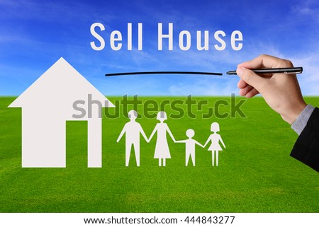 Businessman hand holding pen and message Sell House with model of house and family on green grass field and blue sky background. Business concept in selling, building or purchase house property.  - stock photo