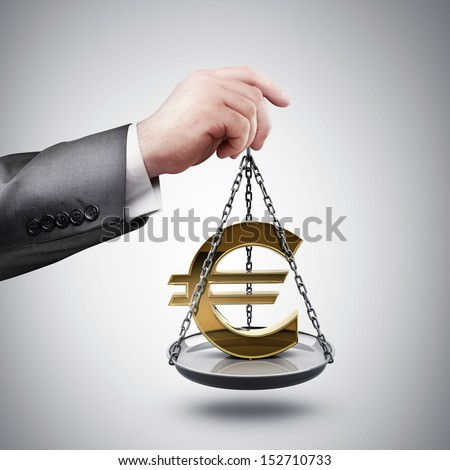 businessman hand holding Scale with symbols of currencies Euro - stock photo