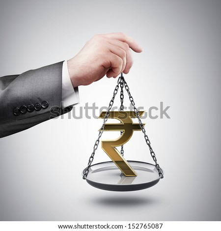 businessman hand holding Scale with symbols of currencies rupee - stock photo