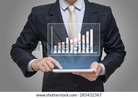 Businessman hand holding tablet graph finance isolated on gray background - stock photo